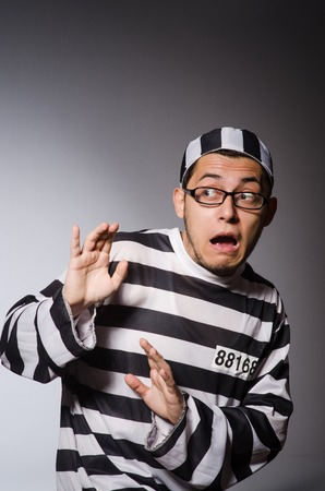 detained: Funny prisoner isolated on gray Stock Photo