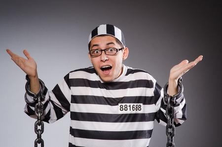 fraudster: Funny prisoner in chains isolated on gray