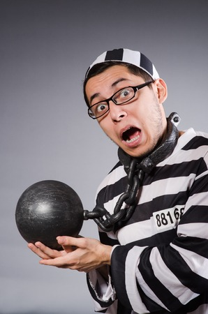 incarceration: Funny prisoner in chains isolated on gray
