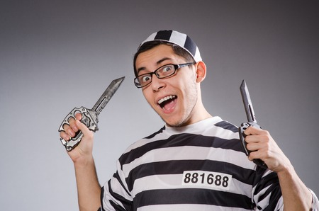 shackled: Funny prisoner with knuckles isolated on gray