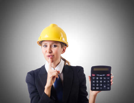 budget repair: Female construction worker with calculator Stock Photo