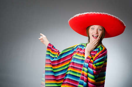 party hat: Girl in mexican vivid poncho against gray