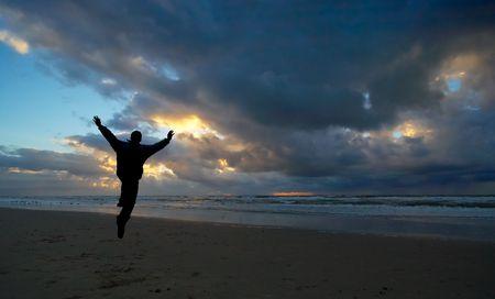Una persona saltando de alegr�a durante la puesta de sol  Foto de archivo - 410835