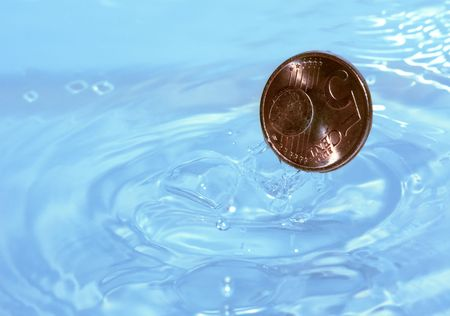 A coin drops into water photo