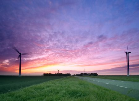 A road and  windmills during sunset, made with a wide angle lens photo