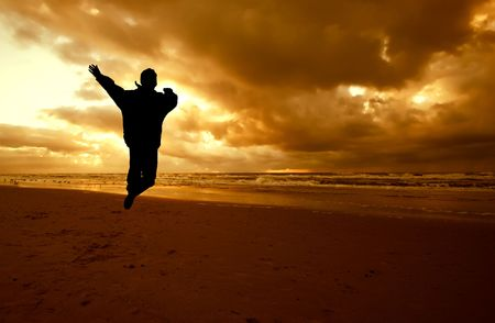 Person jumps in the air on a beautiful night on the beach Stock Photo - 459311