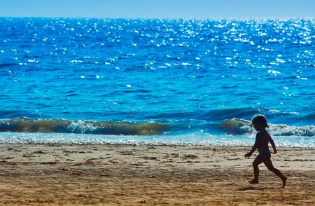 young girl running on the beach in summer Stock Photo