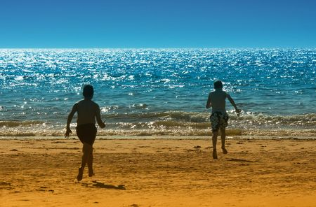 two boys running towards the ocean Stock Photo - 475368