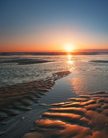 relections on the sand and  sea during sunset