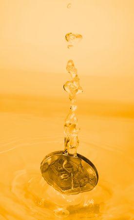 A euro coin drops into a gold liquid photo