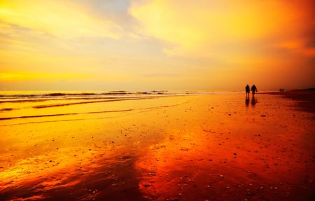 People walking on the beach during sunset
