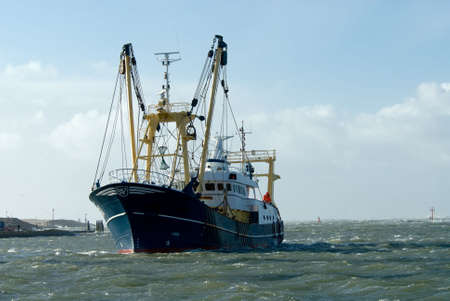 fishing industry: fishing ship during a storm in harbor  Stock Photo