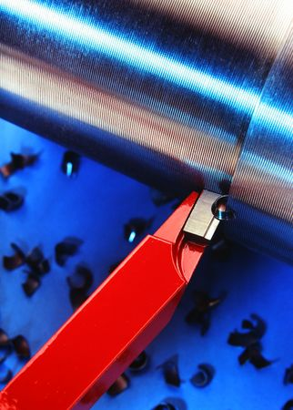 A red industrial tool cutting a shinny pipe over a blue background photo
