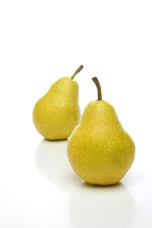 A pair of yellow pears with drops, one on front and one  backwards over a white background. Look for more fruits and vegetables at my gallery photo