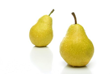 A pair of yellow pears with drops, one on front and one  backwards (out of focus) over a white background. Look for more fruits and vegetables at my gallery photo