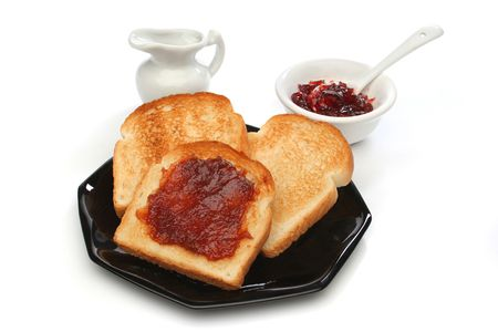 Three toast on a black plate with red jam behind. White background. Deliciuos food for breakfast.  Look at my gallery for more meals photo