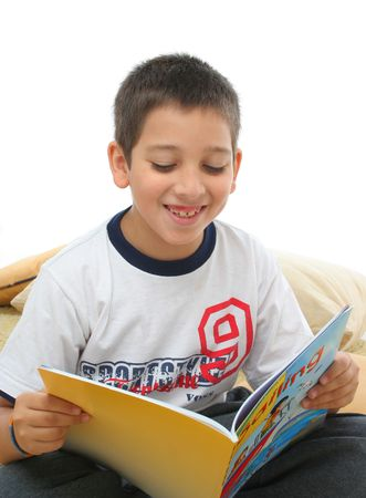 Boy in a room reading a book over a carpet. He is smiling and looks amused. Visit my gallery for more images of children Stock Photo - 387396