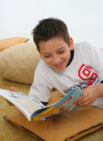 Boy in a room reading a book over a carpet. He is smiling and looks amused. Visit my gallery for more images of children