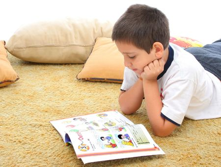 interested: Boy in a room reading a book over a carpet. He looks interested and concentrated. Visit my gallery for more images of children Stock Photo