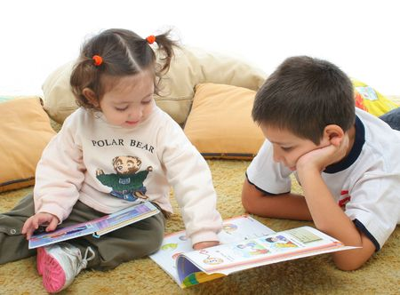 interested: Brother and sister reading books over a carpet. They look interested and concentrated. Visit my gallery for more images of children Stock Photo