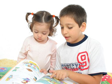 interested: Brother and sister reading a book over a carpet. They look interested and concentrated. Visit my gallery for more images of children Stock Photo