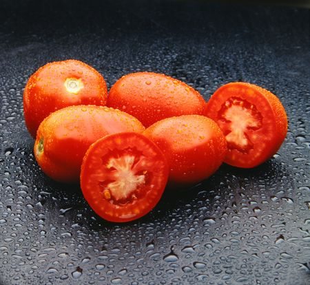 Five red tomatoes with drops over a black surface. Look at my gallery for more fresh fruits and vegetables. photo