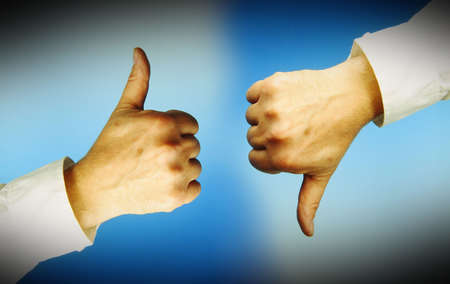 objection: One hand with thumbs up, another with thumbs down. Blue background. Stock Photo