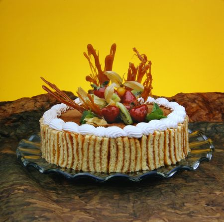 Delicious dessert cake with fruits, cream and chocolate. Good decoration.