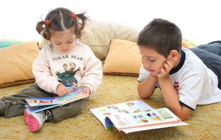 storytime: Brother and sister reading books over a carpet. They look interested and concentrated. Visit my gallery for more images of children Stock Photo