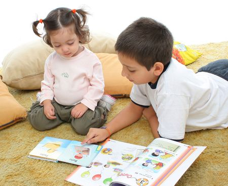 Brother and sister reading books over a carpet. They look interested and concentrated. Visit my gallery for more images of children Stock Photo