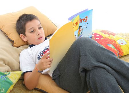 storytime: Boy in a room reading a book over a carpet. He looks interested and concentrated. Visit my gallery for more images of children Stock Photo