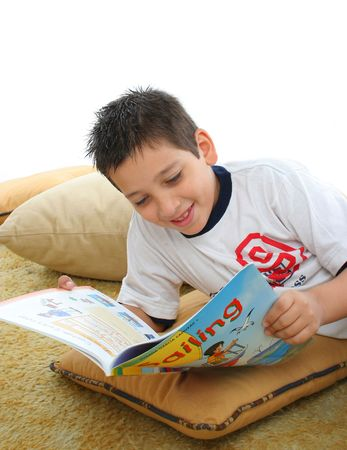 storytime: Boy in a room reading a book over a carpet. He is smiling and looks amused. Visit my gallery for more images of children