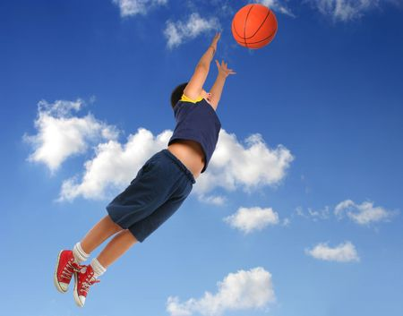 Boy playing basketball isolated. Flying and jumping with blue sky. From my sport series. photo