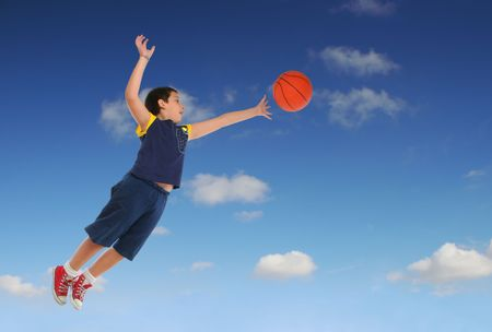 Boy playing basketball jumping and flying. Blue sky. From my sport series. photo