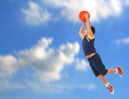 Boy playing basketball jumping and flying. Blue sky. From my sport series.