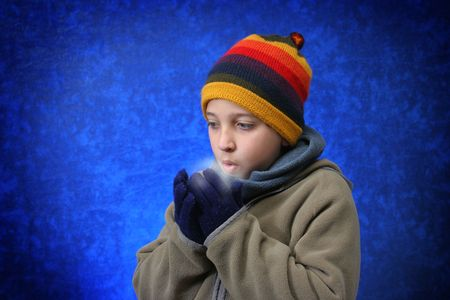 Boy trying to warm his hands with his breath in winter outfit. Look at my gallery for more winter images Stock Photo - 475318