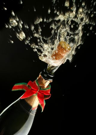 fresh graduate: Champagne splash. Bottle and cork, with christmas decoration Stock Photo