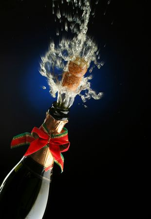 Champagne splash. Bottle and cork, with christmas decoration Stock Photo