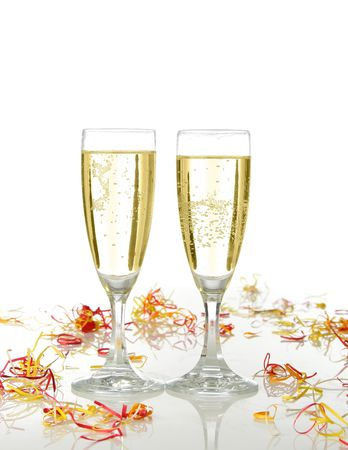 Pair of champagne flutes ready for celebrate. Confetti and white background