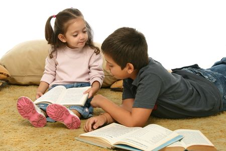 interested: Brother and sister reading books over a carpet. They look interested and concentrated.  Stock Photo