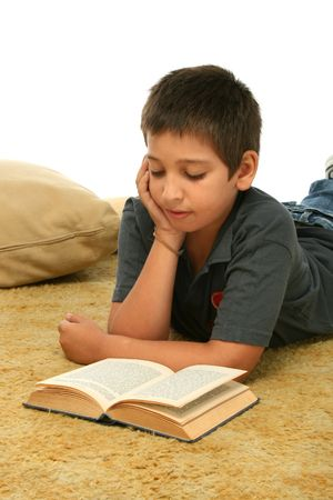 page down: Boy in a room reading a book over a carpet.  Stock Photo