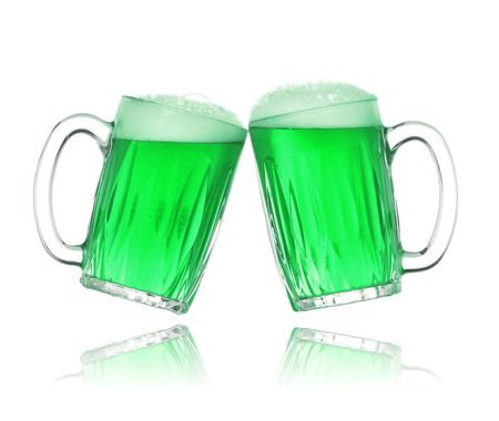 Pair of green beer glasses making a toast. St. Patricks Day beer splash photo