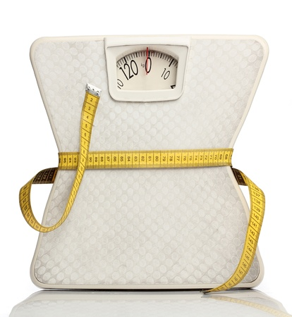 metro de medir: Escala del peso con una cinta métrica sobre blanco Foto de archivo
