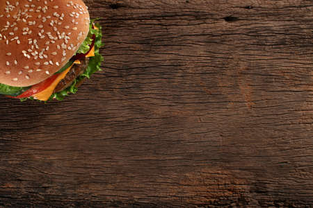 HAMBURGESA: Sabrosa hamburguesa sobre fondo de madera Espacio para el texto Foto de archivo