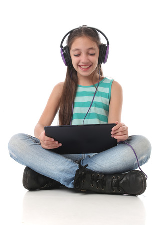 beautiful preteen girl: Beautiful preteen girl using a tablet computer and headphones. Stock Photo