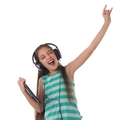 going crazy: Beautiful preteen girl dancing and going crazy using a tablet computer and headphones