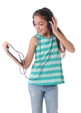 Beautiful preteen girl using a tablet computer and headphones. Isolated photo