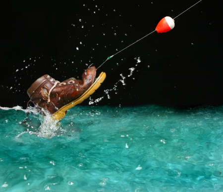 water shoes: Catching an old shoe with a fishing pole. Splash of water Stock Photo