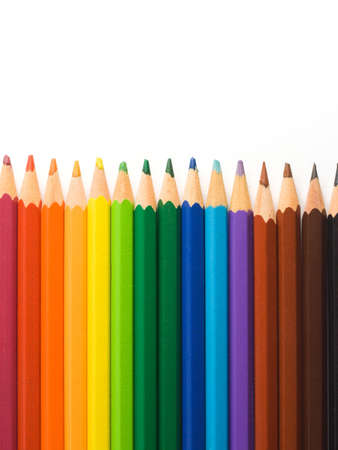 Color pencils aligned in a rainbow pattern on a white background