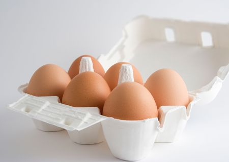 Six eggs in an open box, over a white background
